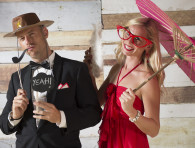 man with cowboy hat, pipe and clouds, woman wit pink umbrella and red big glasses - wedding photo booth at il Borro Tuscany