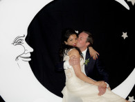 bride and groom sitting on a wooden moon - moonlight set for wedding photo booth