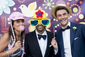 wedding photo booth lo sposo con una coppia di invitati, lui con cappello da clown e occhiali giganti,  loro con labbra e pipa finta