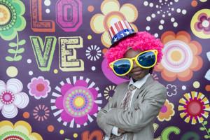 wedding photo booth un bambino con parrucca rosa, occhiali giganti e cappello a stelle e strisce