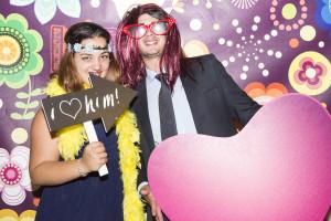 wedding photo booth una coppia di invitati, lui con parrucca da donna e occhiali giganti, lei con coroncina di fiori e lavagnetta con la scritta I Love Him